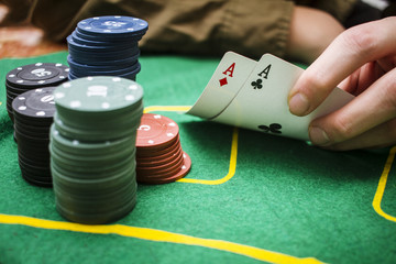 Poker table during a game. Pair aces cards holding in hand. Chips and cards on the table.