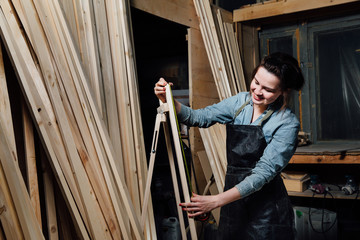 Girl carpenter with a tape measure on a background of wooden pieces in workshop.