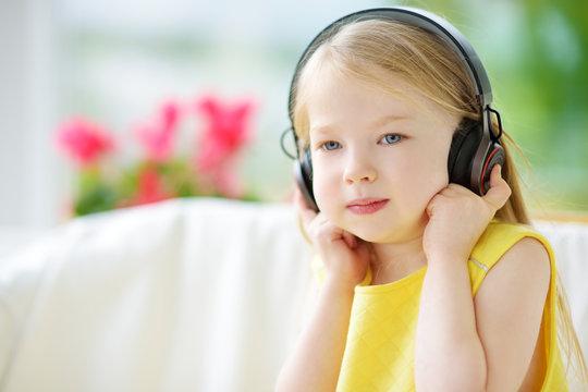 Cute little girl wearing huge wireless headphones. Pretty child listening to the music. Schoolgirl having fun listening to kid's songs at home.
