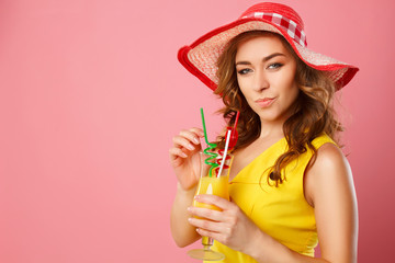Portrait of young beautiful blond woman in red hat with drinking yellow cocktail over pink background