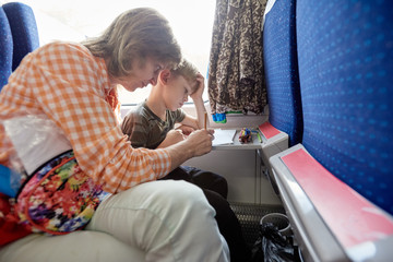 Mother and son traveling. Happy young mother and her kid traveling together by train, mom is engaged in drawing with her son on the train