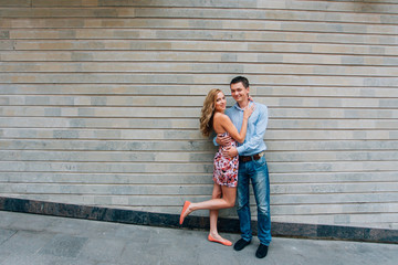 Young happy couple hugging on the street. Smiling man and woman having fun in the city.