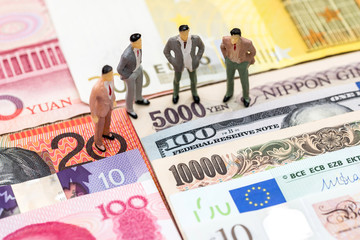 small people on the background of money from different countries