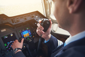 Close up pilot hand taking by portable radio set in cabin while navigating plane. Occupation and communication concept Fototapete