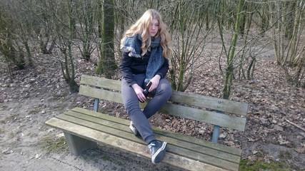 Jugendliche sitzt mit einer Bierflasche auf einer Parkbank
