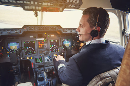 Side view serene pilot talking by headset while situating in cabin with appliances. Appliance concept