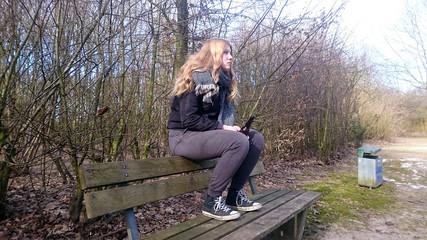 Teenager sitzt mit einer Bierflasche auf der Lehne einer Parkbank, Seitenansicht