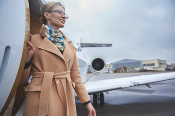 Low angle smiling female going from private airplane. Trip concept