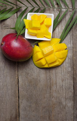 Fresh tropical mango on wooden background.