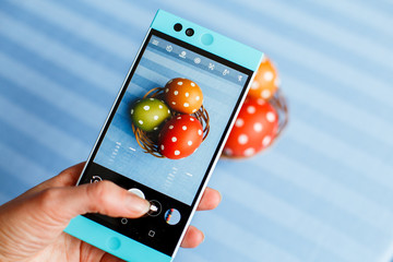 easter, holidays, tradition, technology and people concept - close up of woman hands with smartphone taking picture of colored easter eggs with dots