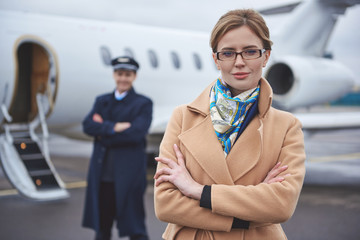 Portrait of glad young female locating opposite private airplane. Pilot situating near it. Profession concept