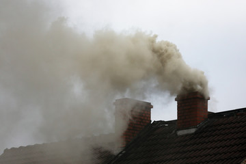 Brown smoke from chimney house due to combustion of coal