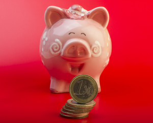 Piggy bank and one euro on a pile of coins. Red background. Cover. Euro money.  Currency of the European Union.