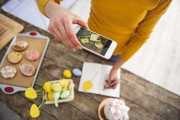 Top view of woman in kitchen making photo of her hand writing in notebook. Basket with pained eggs, cookies and glazed easter cake are standing on table. Focus on cellphone