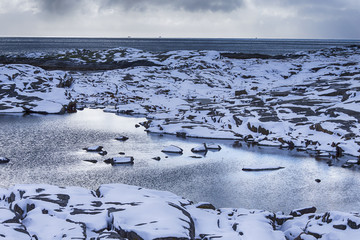 Travel Ideas and Concepts. Snowy and Stony Lofoten Islands Seascape in Norway Separately Covered with Snow.