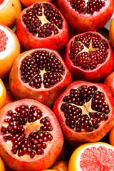 Ripe red garnet with cut up top, pomegranate seeds close-up