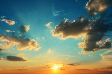 Bright sunset on blue sky with dark clouds.