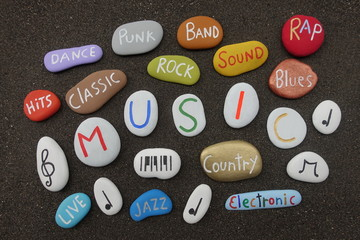 Music cloud with multicolored stones over black volcanic sand