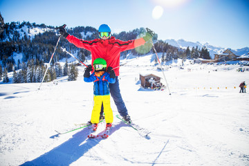 Little boy having fun with his attractive father during skiing in Alps.