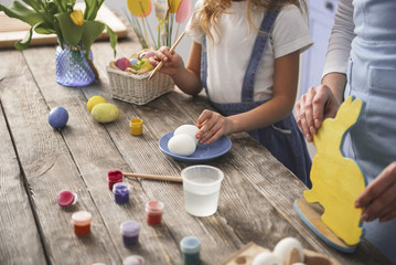 Mother and child hands making different easter decorations on wooden table. Close up