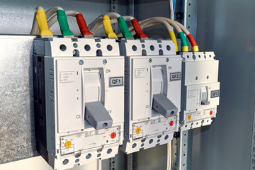 Power circuit breakers are arranged in a row in an electric Cabinet. Cables or marked wires are connected to the switches. The circuit breakers have adjustment.