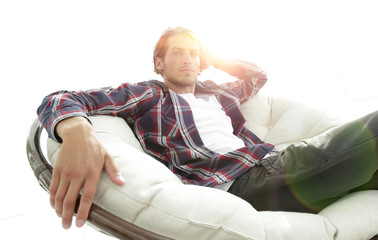 serious guy rests sitting in a large comfortable chair. side view.