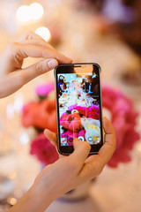 Woman taking a picture of wedding decoration flowers by her phone