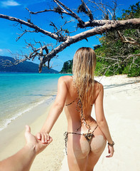 Girl in bikini with wild leopard print holding a hand Man on the paradise beach in Thailand with white sand and say follow me to fairy tale