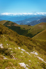 Panoramic View of beautiful landscape in the Italian Alps with fresh green meadows and snow-capped mountain tops in the background on a sunny day with blue sky and clouds in springtime.
