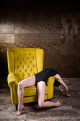 beautiful, sexy Caucasian woman with thin figure and long bare legs, barefoot posing lying down bent back on yellow chair in interior against dark wooden wall. Dressed in black gymnastic swimsuit
