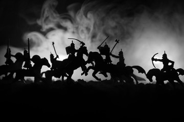 Medieval battle scene with cavalry and infantry. Silhouettes of figures as separate objects, fight between warriors on dark toned foggy background. Night scene.