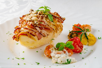 Potato filled with bacon served on plate with baked vegetables and fresh herbs.