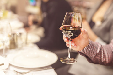 Adult hand holding glass of red whine. Toasting at celebration . Cafe or restaurant background.  Chief speech while corporate business party
