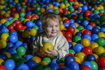 happy little child plays on a playground filled with colorful plastic balls.
