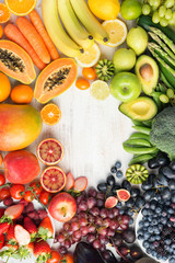 Healthy eating, different varieties of fruits and vegetables in rainbow colours on the off white table arranged in a frame with copy space, top view, selective focus