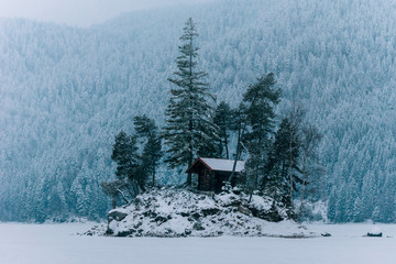 Cabin on an island on a frozen lake with trees and snowy pine forest in the background on a cloudy day at lake Eibsee, Germany