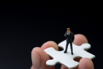 Missing piece person for business success concept, miniature people businessman thinking and standing on  white jigsaw puzzle piece in real human hand with dark black background