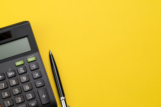 Flat lay or top view of black pen with calculator on vivid yellow background table with blank copy space, math, cost, tax or investment calculation