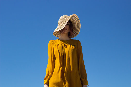 beautiful woman wearing yellow shirt and sun hat on beach dune with blue sky in background