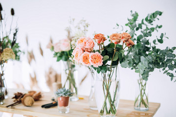 close-up of pink roses in a glass vase on a wooden table on a background of roses, dried cones, greens, scissors, rope, bumps on a white wall background