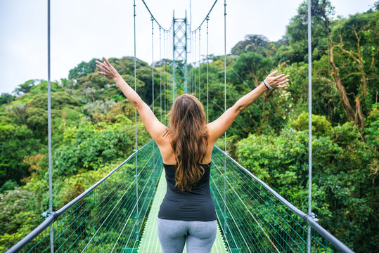 Woman with arms raised on hanging bridges of Costa Rica