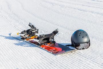 Сноуборд со шлемом на горнолыжном склоне в горах