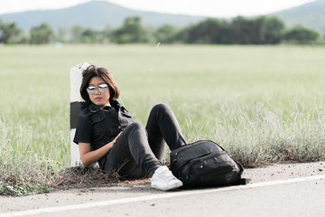 Woman sit with backpack hitchhiking along a road