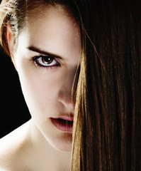 Close up of beautiful young woman with half her face hidden by long hair