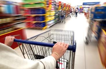 Women pushing trolley cart in supermarket