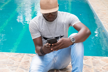 Man using smartphone at the poolside