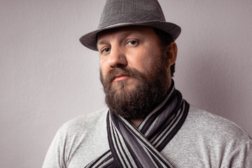 Bearded young hipster man wearing gray hat and scarf, fashion portrait against gray wall.