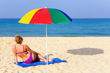 Lonely girl on the beach under a colorful umbrella.