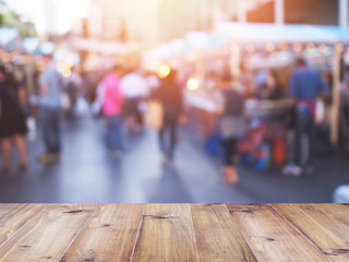 table top over blurred background of people shopping at market fair