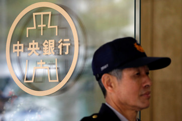 Police officer stands beside the Taiwanese Central Bank logo in Taipei